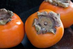 Sharon Fruit. Three sharon fruit against a black background Stock Images