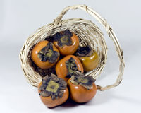 Sharons in a basket. Sharons/persimmon in a wicker basket Royalty Free Stock Photography