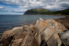 The sharp and angular rocks on the shore of the bay. Royalty Free Stock Photo