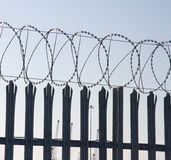Sharp barbed wire spiral. Against grey sky and part of a fence Stock Image