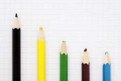 Sharp black pencil. And four colored blunt pencils on the squared paper sheet Royalty Free Stock Photography