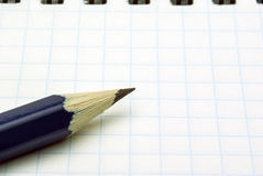 Sharp blue pencil. On the background of the sheet in a cage Stock Photos