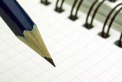Sharp blue pencil. On the background of the sheet in a cage Stock Photo