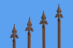 Sharp bronze fence isolated on blue. Four Sharp bronze fence rail isolated on blue Stock Photo