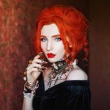Sharp claws. Dark halloween attire. Sorceress woman is vampire with pale skin and red hair in black dress and necklace on neck. Girl sorceress with vampire royalty free stock photo