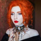 Sharp claws. Gothic halloween attire. Unusual woman pray with pale skin and red hair in black dress and necklace on neck. Unusual girl sorceress pray with stock photos