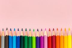 Color crayons in equal order. Sharp color crayons in equal order on pink background with copy space no people Stock Photo
