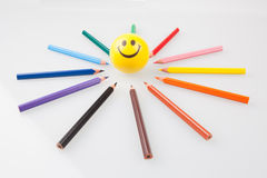 Sharp colorful pencils pointing at smiley face Stock Photo