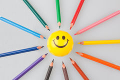 Sharp colorful pencils pointing at smiley face Royalty Free Stock Photo