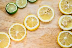 Sharp and contrast image of lemon slice. Top view to fresh organic lemon slice isolated on wood cutting board with clipping path. royalty free stock image