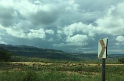 Sharp curve ahead. Roadside shot with storm clouds stock photos