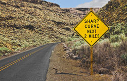 Sharp Curve Next 2 Miles Sign. Not sure how sharp a curve is if it is 2 miles long Royalty Free Stock Photo
