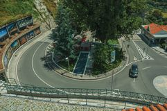 Sharp curve in a road around trees with car. Manteigas, Portugal - July 14, 2018. Sharp curve in a road around trees with car, in a sunny day at Manteigas. It is stock image