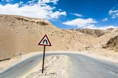 Sharp curve on the road in Ladakh, India. Sharp curve with sign on the road in Ladakh, India stock photo