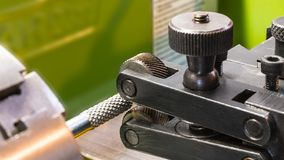 Two wheel knurling tools when working on a lathe. Sharp cutting wheels for grooving. Machining of a metal workpiece clamped in the machine-tool chuck. Idea of stock images