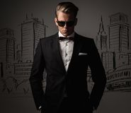 Sharp dressed man in black suit against city Stock Images