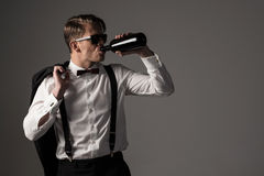 Sharp dressed man in black suit with bottle of wine Stock Photo