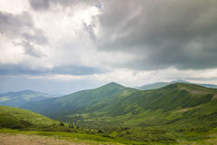 Sharp green mountain peaks and sky with dramatic clouds landscap Stock Images