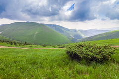 Sharp green mountain peaks and sky with dramatic clouds landscap Stock Photography