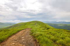 Sharp green mountain peaks and sky with dramatic clouds landscap Stock Photos