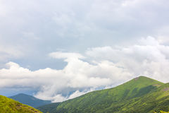 Sharp green mountain peaks and sky with dramatic clouds landscap Royalty Free Stock Images