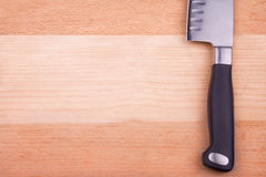 Sharp knife on cutting board. Big sharp shiny knife is lying on wooden cutting board Stock Photos