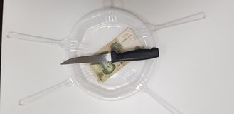 Sharp knife on empty white plastic plate over one china money banknote. Near five disposable transparent forks stock image