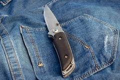 A sharp knife on a jeans background in nature. royalty free stock image