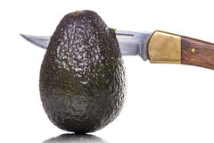 Sharp knife  stings through an avocado Royalty Free Stock Photo