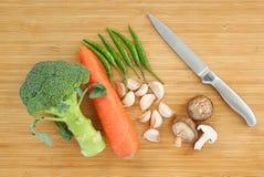 Sharp knife with Vegetable Shiitake mushroom, chilli, carrot, broccoli, garlic on wooden block.  Stock Photography