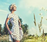 Sharp looking blonde walking through meadow. Stock Image