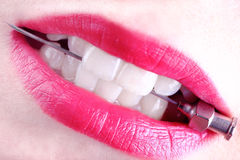 Sharp medical needle in the white teeth of a young woman Stock Image