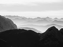 Sharp mountain silhouettes. Distant mountain range and heavy clouds of colorful mist Royalty Free Stock Images