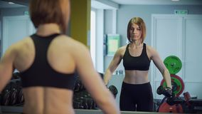With sharp movements a woman raises her arms with dumbbells up for doing sport. The athlete raises two direct arms with dumbbells upwards for the development of stock video footage