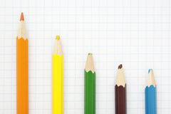 Sharp  orange  pencil. And colored blunt pencils on a writing-book leaf Royalty Free Stock Images