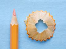 The sharp orange pencil is ready for drawing. Orange pencil with a shavings on a blue background. Concept of education or back to school. Top view, flat lay royalty free stock image