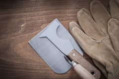 Sharp paint scraper bricklaying trowel and leather safety gloves Stock Images