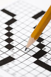 A sharp pencil on a crossword puzzle Royalty Free Stock Images