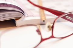 Sharp pencil in focus, eyeglass and crossword. Sharp pencil in focus, eyeglass and crossword close up macro shot Royalty Free Stock Images