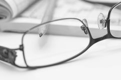 Sharp pencil in focus, eyeglass and crossword. Sharp pencil in focus, eyeglass and crossword close up macro shot in black and white Royalty Free Stock Photography