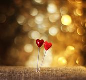 Two sharp pins in the form of red hearts stuck in the burlap on Stock Photography