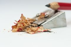 Sharp red pencil, sharpener, focus on the waste . Sharp red pencil, sharpener, focus on the waste isolated on white background Stock Images