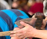 A sharp reflection. Wood chopping competitor honing his shiny axe stock photography