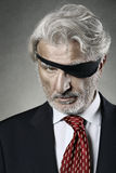 Sharp and resolute one eye gaze. Sharp and resolute gaze from one eyed manager . Ruthless leadership Royalty Free Stock Photo
