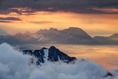 Sharp ridges above sea of clouds illuminated by rising red sun. Sharp ridges of Karavanke and Kamnik Savinja Alps tower above sea of clouds and morning mist Stock Photos