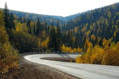 Sharp road bend in autumn forest. Sharp road bend in autumn ural mountains stock photo