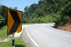 Sharp road curve sign. Right arrow Street sign around the of mountain road bend in Cameron Highlands, Malaysia royalty free stock image