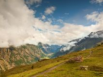Sharp snowy peaks of Alps mountains above valley full of heavy fog, end of summer Royalty Free Stock Photos