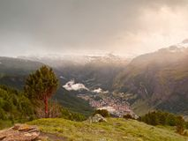 Sharp snowy peaks of Alps mountains above valley full of heavy fog, end of summer Stock Images