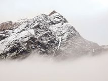 Sharp snowy peaks of Alps mountains above valley full of heavy grey  fog Stock Photos